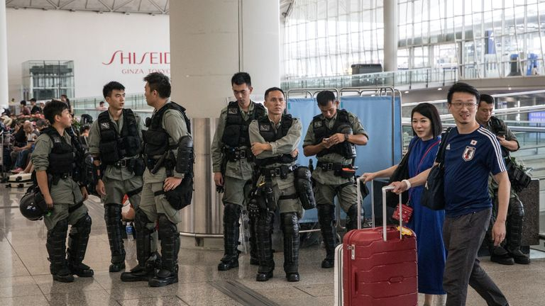 Passengers walk past police guarding the entrance to Hong Kong International Airport