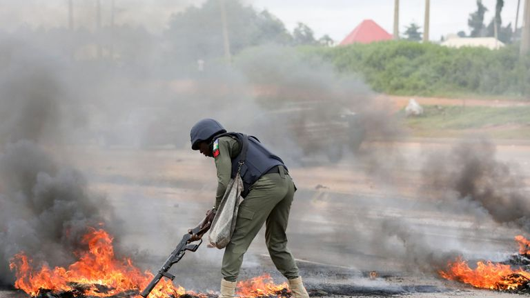 A policeman tries to remove a bonfire outside a South African-owned supermarket in Nigeria