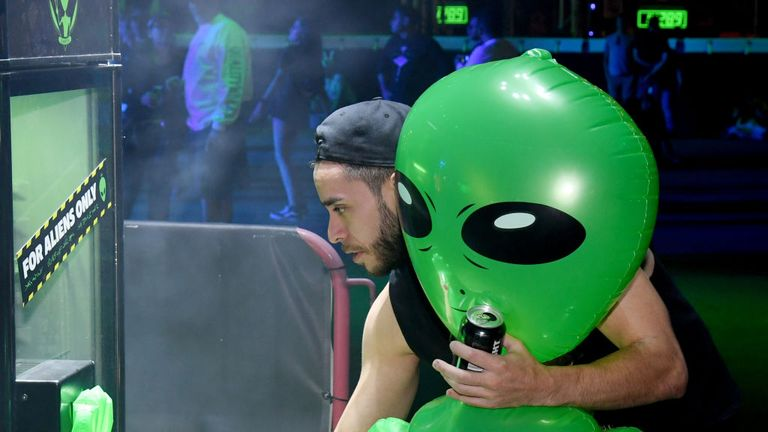 Revellers joke around with an inflatable alien during an Area 51 Celebration in Las Vegas on Thursday