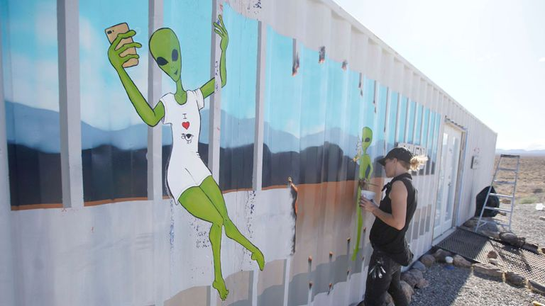An artist paints the side of a building near the Storm Area 51 event this weekend