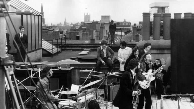 30th January 1969: British rock group the Beatles performing their last live public concert on the rooftop of the Apple Organization building for director Michael Lindsey-Hogg's film documentary, 'Let It Be,' on Savile Row, London, England. Drummer Ringo Starr sits behind his kit. Singer/songwriters Paul McCartney and John Lennon perform at their microphones, and guitarist George Harrison (1943 - 2001) stands behind them. Lennon's wife Yoko Ono sits at right