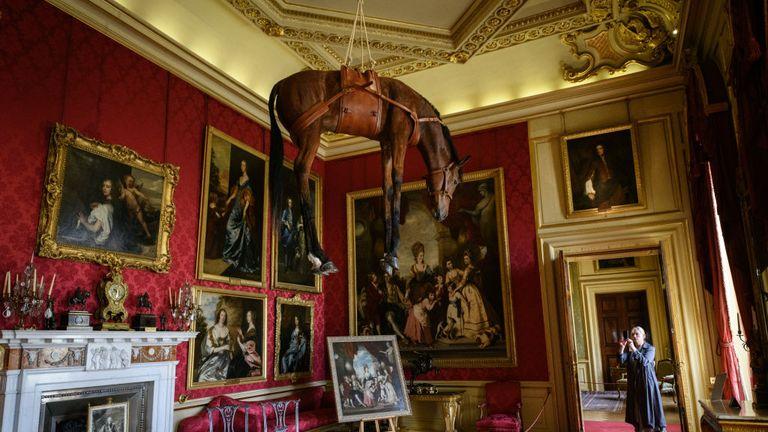Un cal de taxidermie suspendat din plafonul istoric ca parte a expoziției dlui Cattelan & # 39;