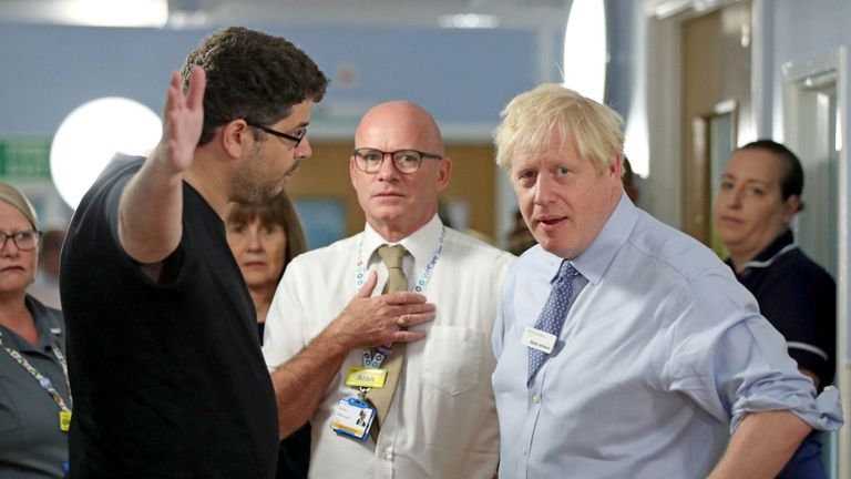 Boris Johnson meets the father of a young girl, who is being treated in the Acorn Children's Ward, during a visit Whipps Cross University Hospital in Leytonstone