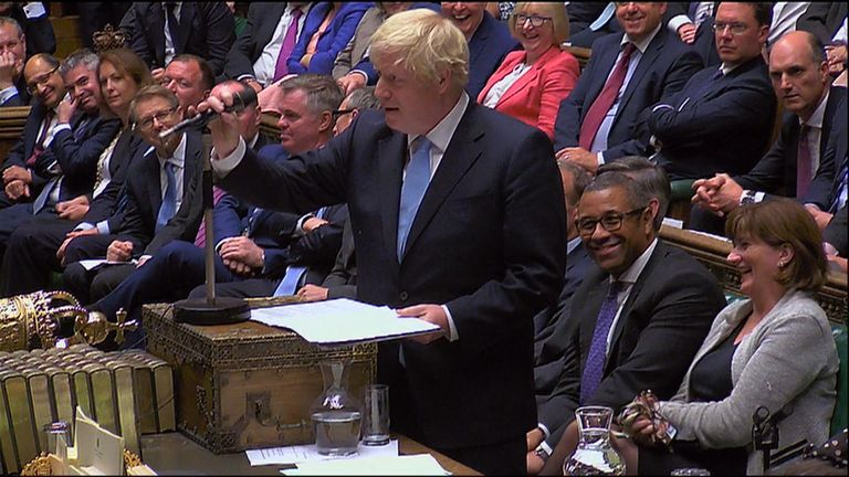 Amid the noise in the Commons chamber, Johnson lifts up the microphone in front of him and places it on top of the despatch box