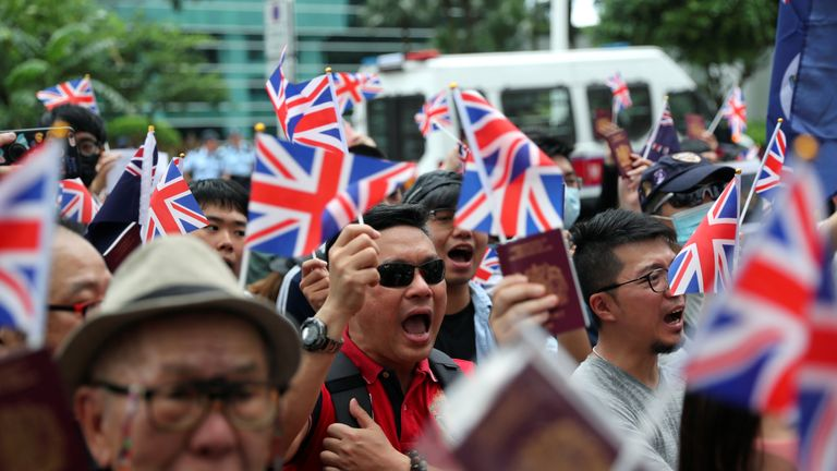 Protesters wave Union Jack flag and hold up their passports outside the British Consulate in Hong Kong