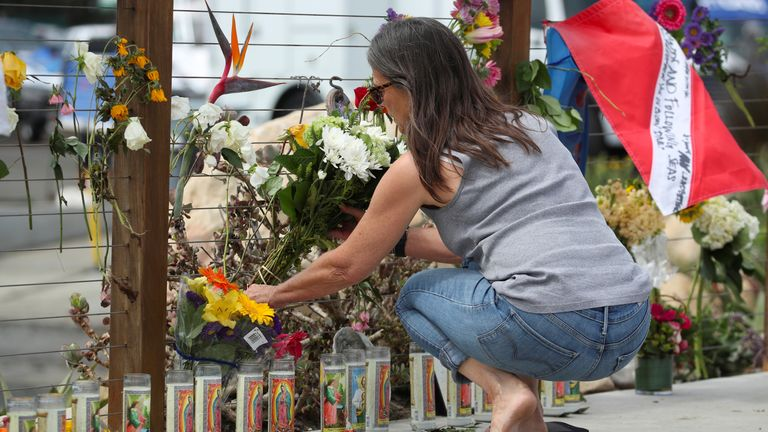 A woman places flowers at a makeshift memorial in Santa Barbara for the 34 victims of the boat disaster
