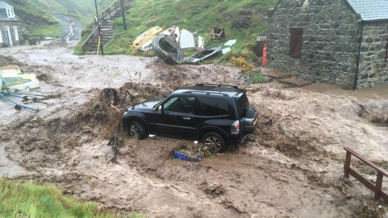 A car stuck in mud after heavy rain in Crovie, Aberdeenshire