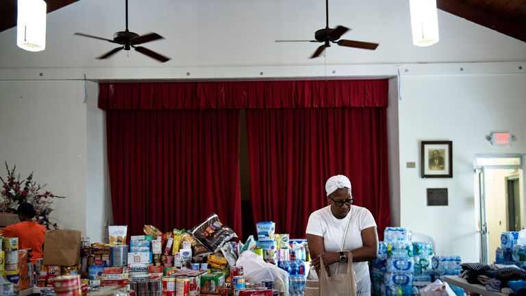 A woman carries a bag of canned goods as donations for Hurricane Dorian relief are received at a church in Miami, Florida