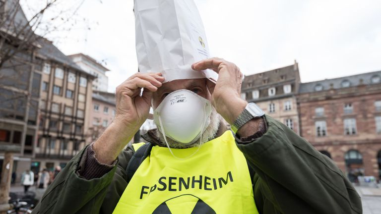 A man dons a mock nuclear survival kit during a demonstration demanding the closure of the Fessenheim nuclear powerplant on February 3, 2018 in Strasbourg