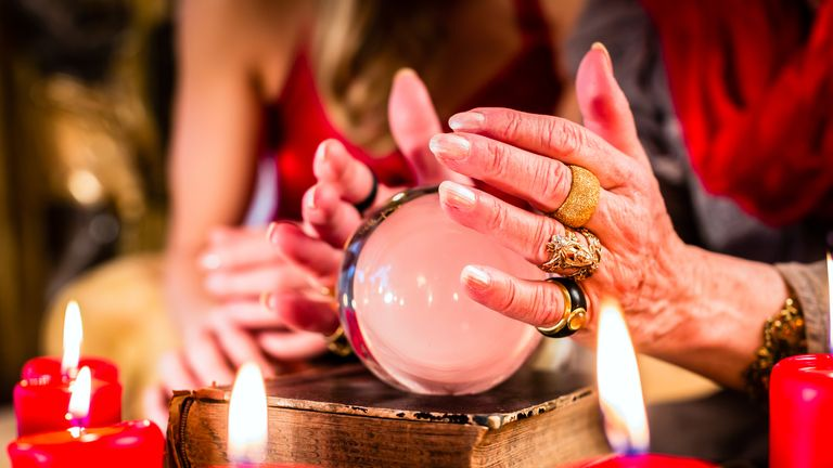 Female Fortuneteller or esoteric Oracle, sees in the future by looking into their crystal ball during a Seance to interpret them and to answer questions (Female Fortuneteller or esoteric Oracle, sees in the future by looking into their crystal ball du