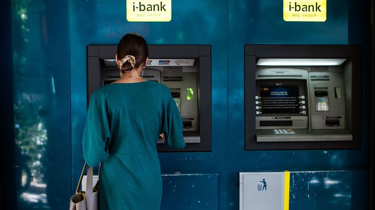 A woman withdraws cash from an ATM machine in Athens on August 26, 2019. - Greek Prime Minister Kyriakos Mitsotakis told parliament on August 26, 2019 that the country would end capital controls imposed four years ago