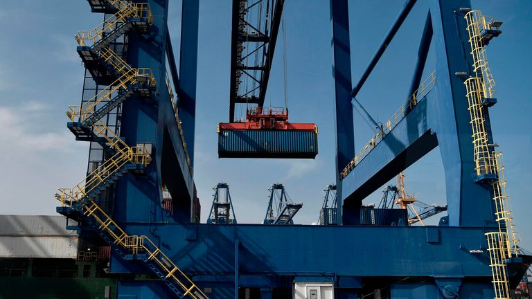 Cranes load a container at the new container terminal in the port of Piraeus on October 18, 2018. - Chinese shipping giant Cosco said it has ambitious plans for the Greek port of Piraeus