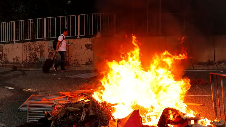 A man passes by a burning barricade near the airport