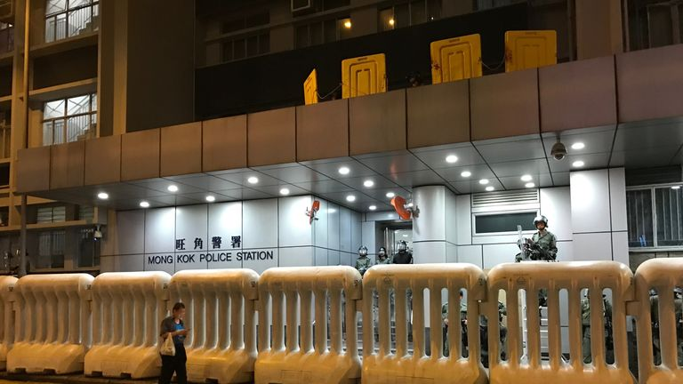 Armed officers watched the protesters from behind barricades