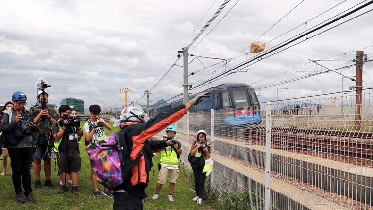 A protester is seen throwing a rock onto train tracks near the airport