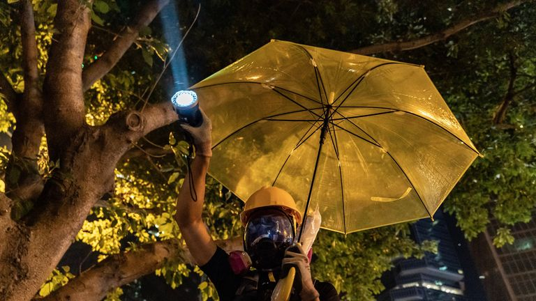 A pro-democracy protester points a flashlight at police during a stand-off outside the Central Government Complex on September 28, 2019 in Hong Kong, China