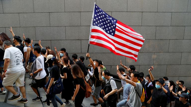 Protesters hold up five fingers and a US flag as they marched to the US Consulate General in Hong Kong