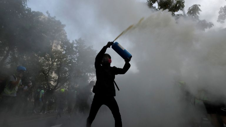 An anti-government protester uses a fire extinguisher