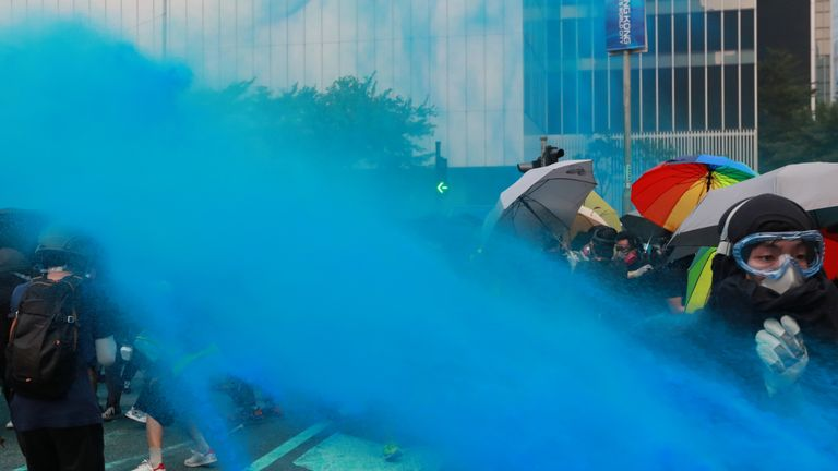 Blue-coloured water is sprayed towards anti-government protesters during a demonstration