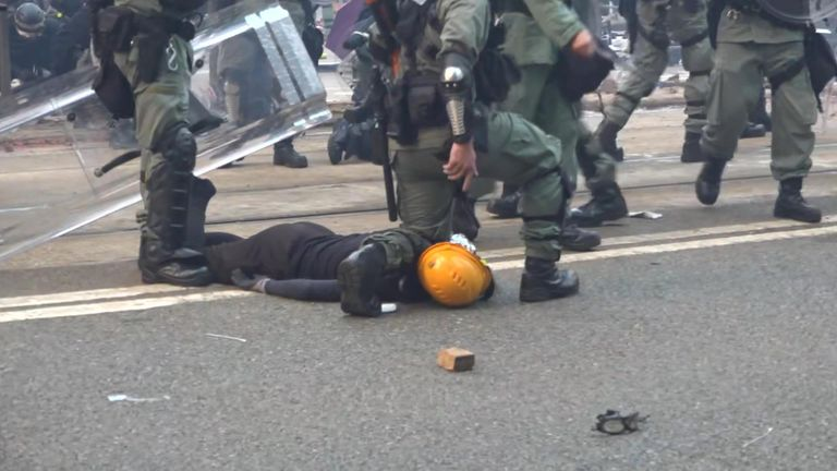 A police officer kneels on a protester