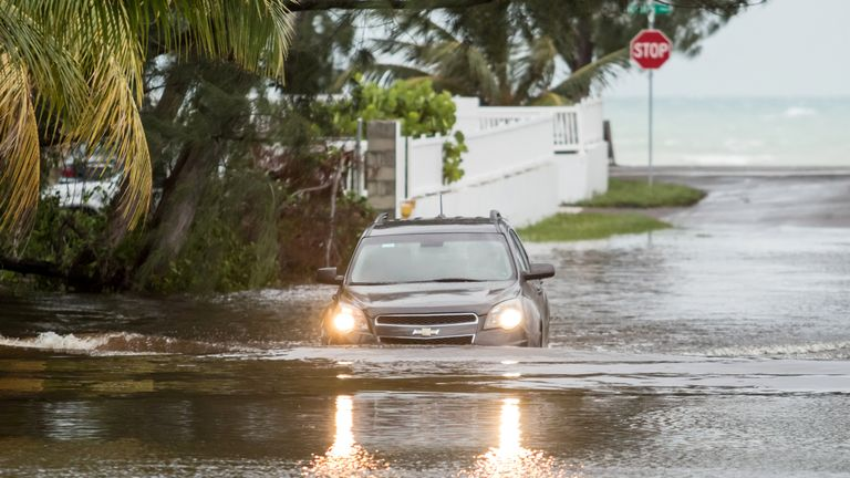 A car drives through a flooded street after the effects of Hurricane Dorian arrived in Nassau, Bahamas