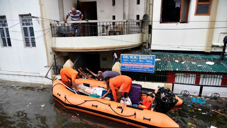 Boats have been rescuing people from flooded neighbourhoods
