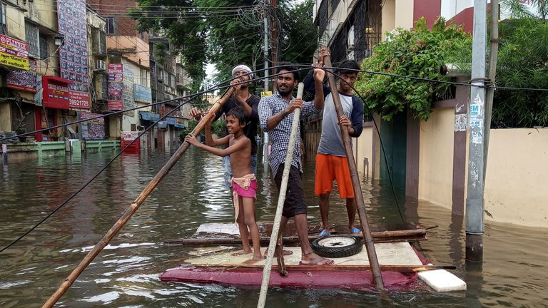 People used a makeshift raft to move out of a flooded neighbourhood in Patna