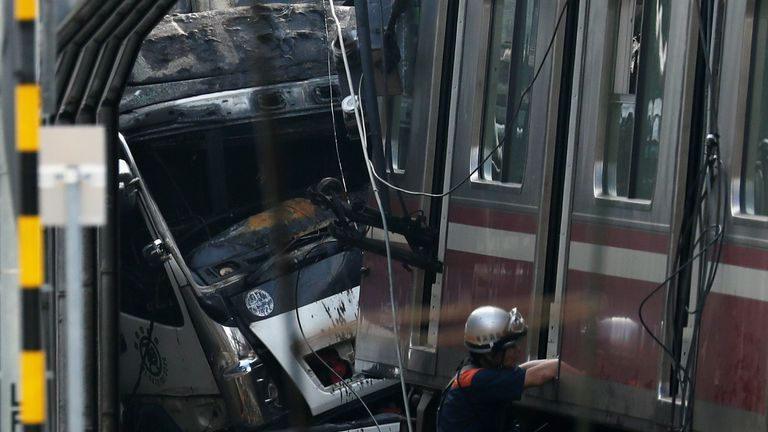 Rescue officers, police and railway company employees work at the scene after the train derailed during a collision with the truck in Yokohama, near Tokyo