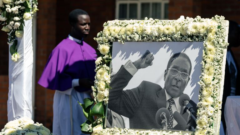 A priest walks past a portrait of Robert Mugabe during the burial of the former Zimbabwe leader at his home village in Kutama, on September 28, 2019