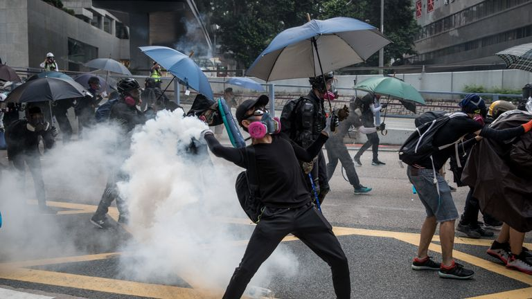 A pro-democracy protester throws a tear gas canister back at police