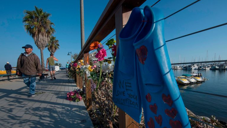 Flowers and diving equipment placed on a memorial wall to those who died