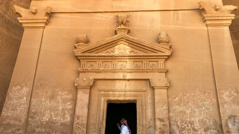 A Saudi tour guide stands inside a tomb at the Madain Saleh antiquities site, in al-Ula, Saudi Arabia