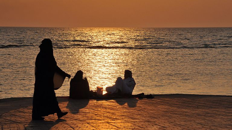 Saudi families spend an evening by a seafront promenade as the sun sets in the Red Sea city of Jeddah