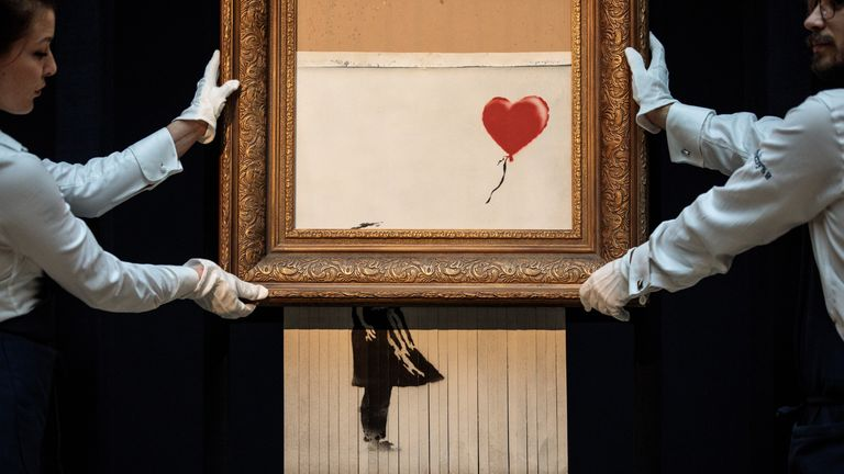 Sotheby's employees pose with 'Love is in the Bin' by  Banksy