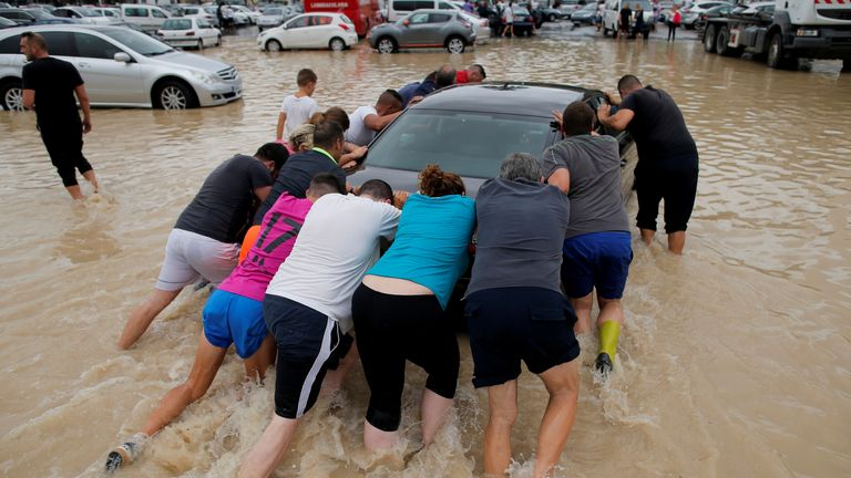 People push a car through a partially submerged parking as torrential rains hit Orihuela, Spain