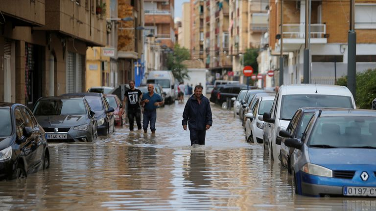 People wade through a flooded street as torrential rains hit Orihuela