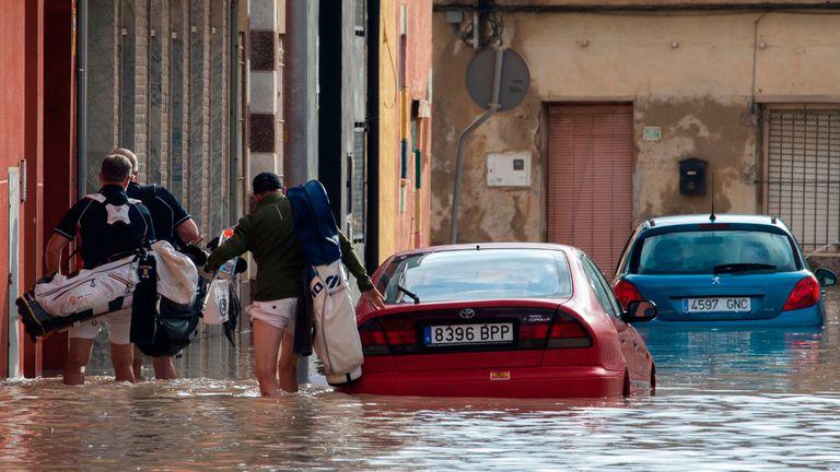 People walk on a flooded street in Almoradi