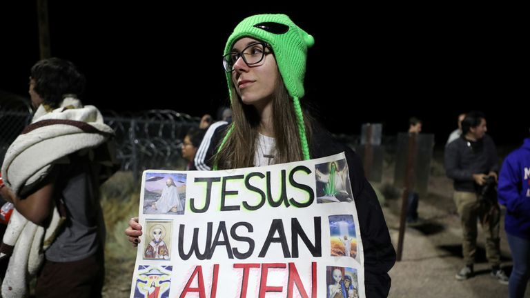 A person carries a sign outside a gate to Area 51