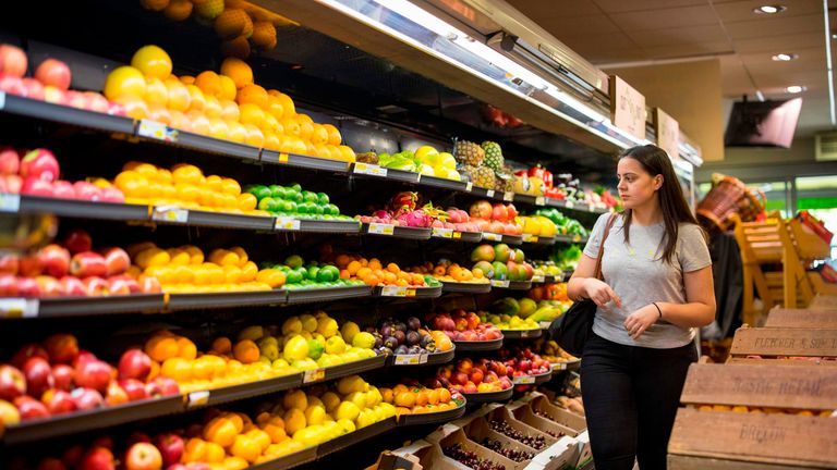 People browse the shelves with loose un-packaged fruit