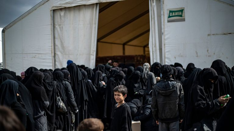 Iraqi refugees and displaced Syrian women, living in al-Hol camp which houses relatives of Islamic State (IS) group members, queue to receive goods in the camp in al-Hasakeh governorate in northeastern Syria on March 28, 2019