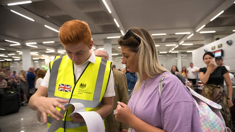 A British Government official talks to a Thomas Cook passenger at Son Sant Joan airport in Palma de Majorca