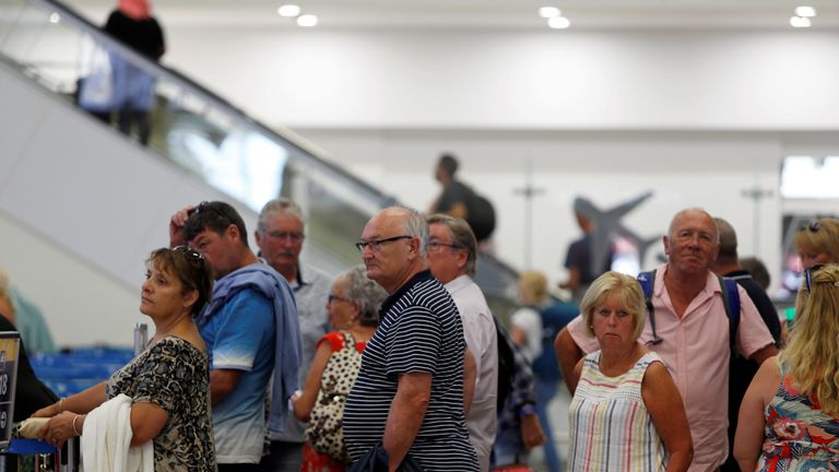 Thomas Cook passengers queue up in a check-in service after the collapse of the travel firm, at Malta International Airport