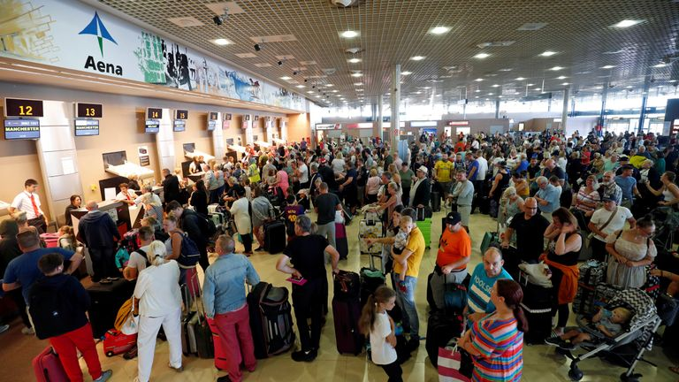 Thomas Cook passengers queue in front of check-in desks on the second day of repatriations at Reus airport in Spain