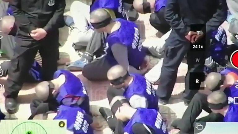 Похоже, что кадры показывают сотни заключенных с завязанными глазами и кандалы в мусульманском регионе Китая.