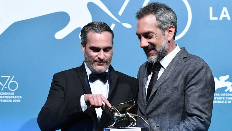 Todd Phillips (r), flanked by Joaquin Phoenix, holds the Golden Lion at the Venice Film Festival