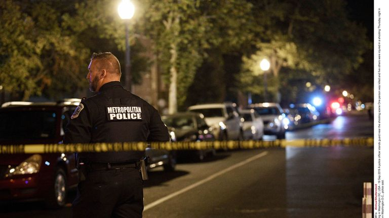 A police officer stands guard near the scene of the shooting