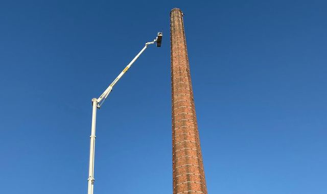 Police continue mission to rescue man dangling from 290ft chimney