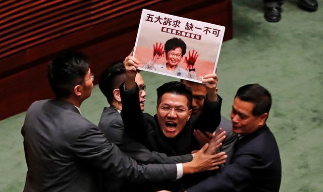 HK politicians dragged out of parliament after activist attacked