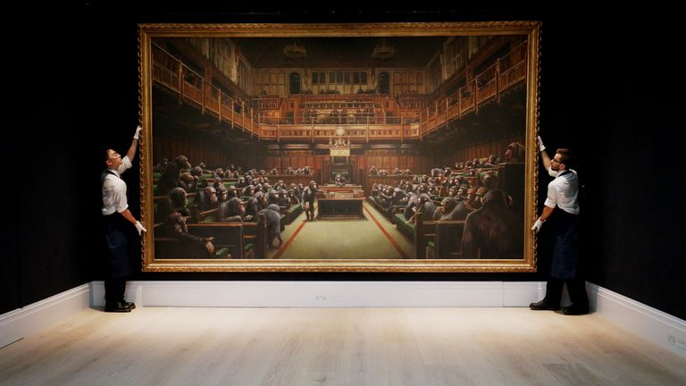 File photo dated 27/09/19 of Sotheby's gallery assistants handling Banksy's Devolved Parliament painting. The piece, a derisive portrayal of the House of Commons, sold at auction for ??9,879,500. The price went well beyond the previous record for the artist at $1.8m million.
