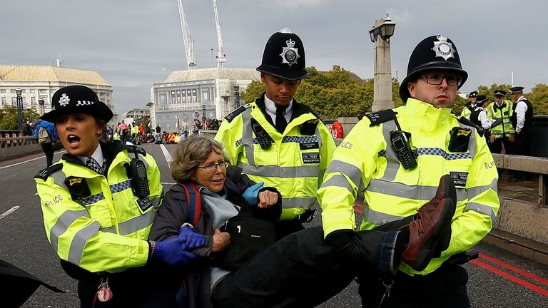 Police officers detain an activist at Lambeth Bridge during the Extinction Rebellion protest in London, Britain October 7, 2019. REUTERS/Henry Nicholls